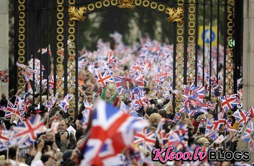 People wave British flags outside Buckingham Palace during the wedding of Britain