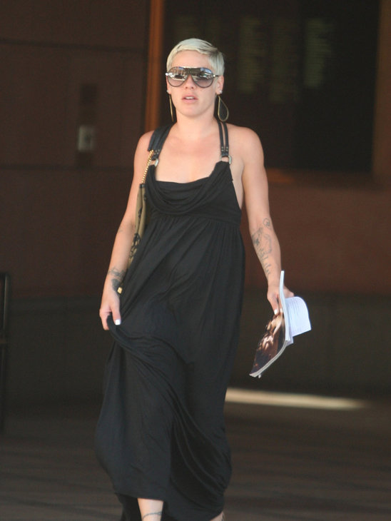 Pink in her classic style, a black mazi-dress kickass sunglasses and wedge heel sandals
