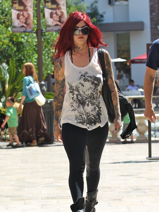 Kat Von D shows off her tattoos in a printed tank, leggings and edgy worker boots