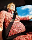 Topošā māmiņa pie automašīnas stūres.